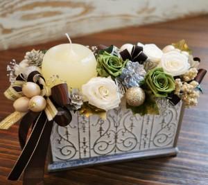 アラベスク模様とシルバー箔が美しい陶器にシックな色合いの花とリボンを盛り込みます。グリッターアイテムのクールな輝きとキャンドルの温かみが響きあう洗練されたデザイン。